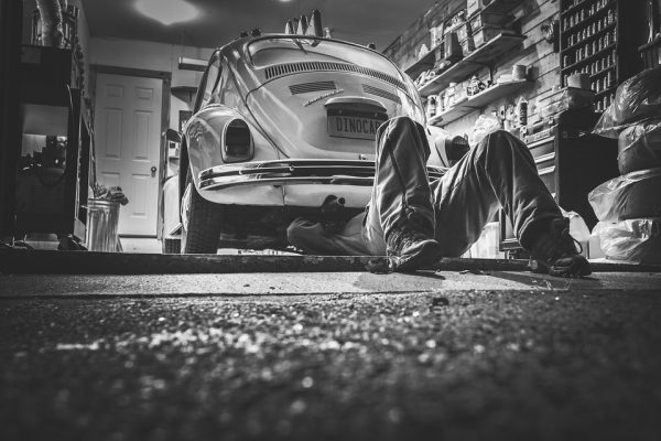 Black and white image of a mechanic under a car