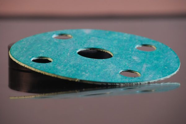 Close up of a green gasket made of asbestos