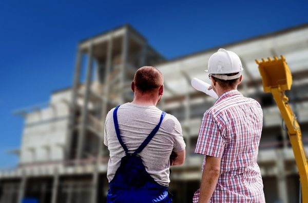 Builders pointing at a building